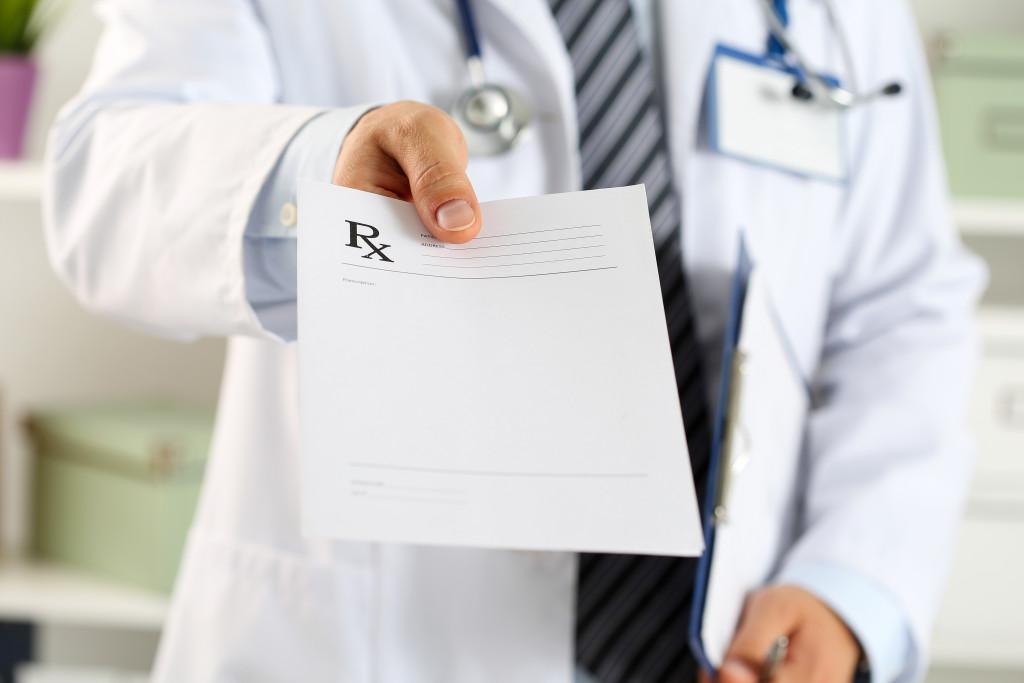 doctor handing out prescription